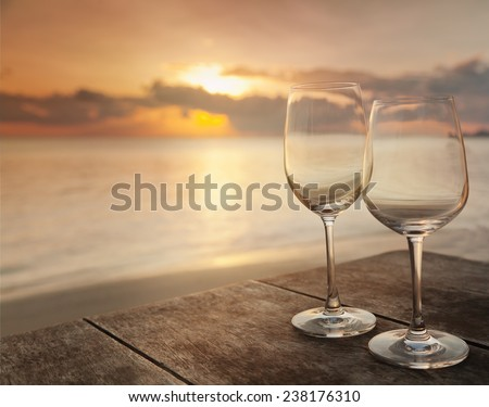 two empty glasses on a table in a cafe on the background of the setting sun - stock photo