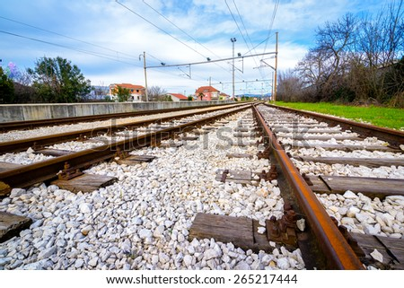 Two empty railway lines joining in the distance - stock photo