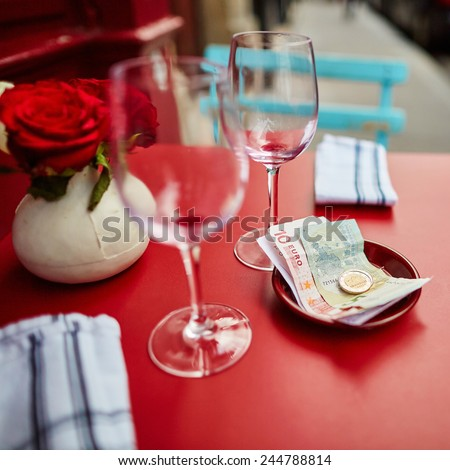 Two empty wine glasses and tip in an outdoor Parisian restaurant, focus on money - stock photo