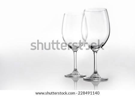Two empty wine glasses close up isolated white. - stock photo
