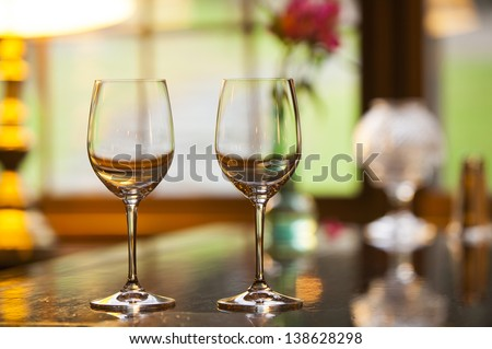 Two empty wine glasses sitting in a restaurant on a warm sunny afternoon. - stock photo