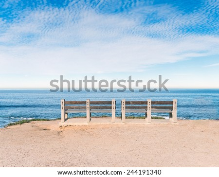 Two empty wood benches on cliff top overlooking the ocean. Blue sky and clouds with horizon view. Room for text, copy space.  - stock photo