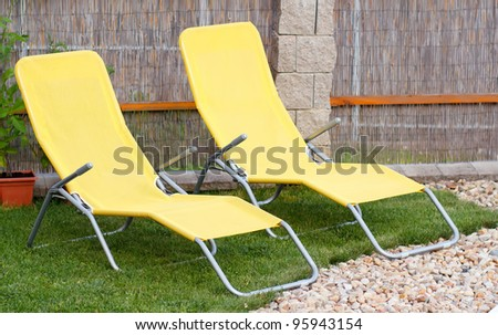 Two empty yellow sun loungers on a garden - stock photo