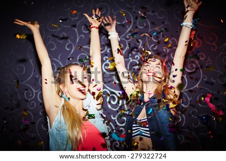 Two energetic girls dancing with raised arms - stock photo