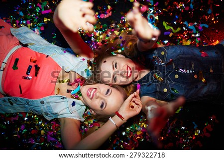 Two energetic girls with raised arms looking at camera in nightclub - stock photo