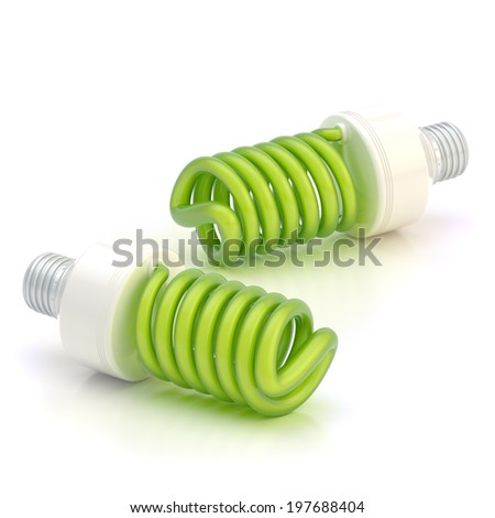 Two energy saving green bulbs lying over the white reflective surface - stock photo