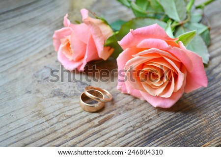 Two engagement golden rings on a beautiful wedding bouquet of pink roses - stock photo