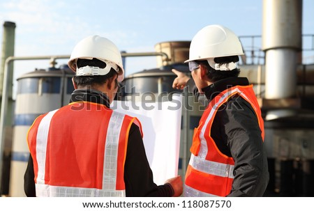 two engineer  discussing a new project with large industry background