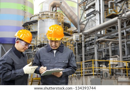 two engineer discussing a new project with large industry background - stock photo