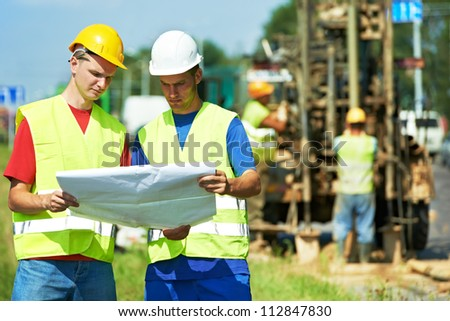 Two engineer site managers builders with blueprint plan at geology roadwork construction site - stock photo