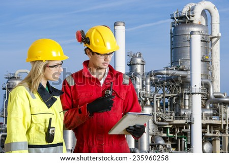 Two engineers going through routine checks, working at a petrochemical oil refinery using cb radios and a tablet computer - stock photo