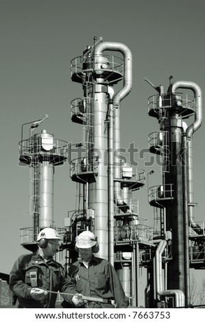 two engineers in front of oil and gas refinery, industry, all in a toning idea - stock photo