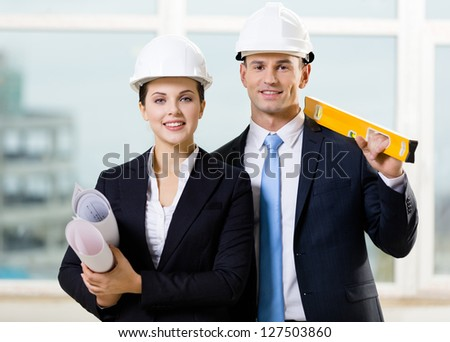 Two engineers in white hard hats keeping level and blueprints. Concept of successful construction - stock photo