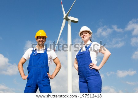 Two engineers or installers posing in front of wind energy turbine