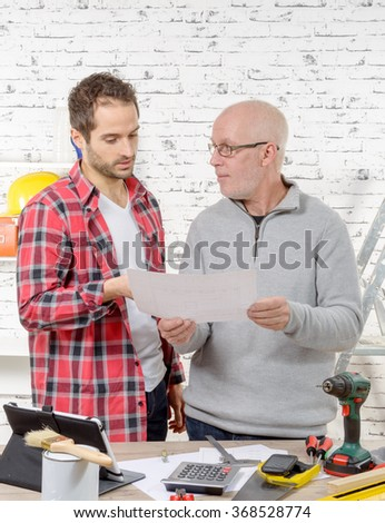 two engineers reading a plan in their office - stock photo
