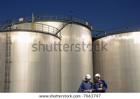 two engineers standing in front of three large refinery storage tanks - stock photo
