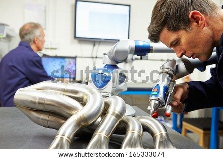 Two Engineers Using Computerized CMM Arm In Factory - stock photo