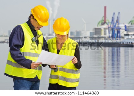 Two engineers, wearing safety gear, including goggles, hard hat, ear plugs and reflective safety vests, discussing blue prints in an industrial harbor with factories and plants in the background - stock photo