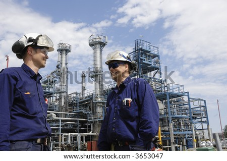two engineers with hard hats and protective clothing in front of large oil-refinery - stock photo