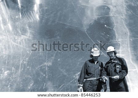 two engineers, workers, set against steel oily background, conceptual shot. - stock photo