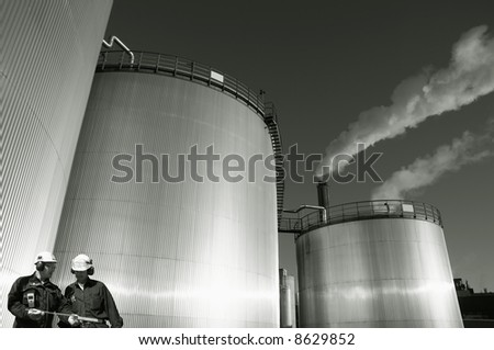 two engineers working in front of refinery oil tanks, toning concept i duplex colors - stock photo