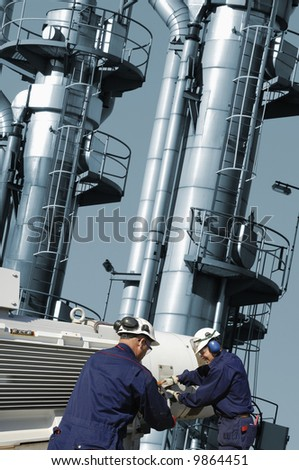 two engineers working on main pipeline pump, blue toning concept - stock photo