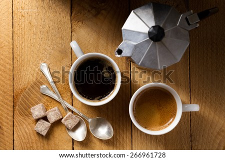 Two espresso and a coffee maker on a rough wooden table (top view) - stock photo