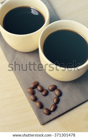 Two espresso coffees in small white cups,with a coffee bean resting on the wood background