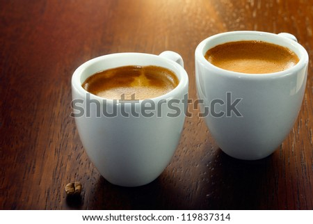 Two espresso coffees in small white cups,with a single coffee bean resting on the wood background - stock photo