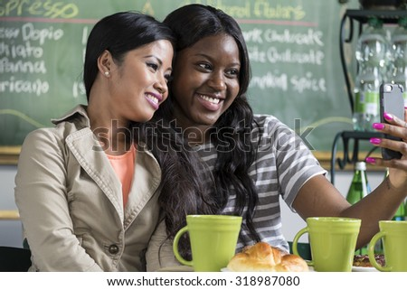 Two ethnically diverse women taking their photo with a cellphone in a cafe - stock photo