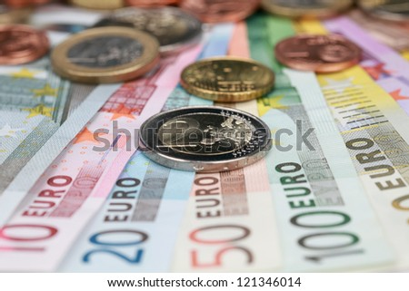 Two Euro coin on Euro banknotes forming a money background - stock photo