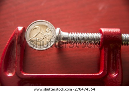 two euro in the clamp coin of 2 euro tightened up in a G-clamp, financial crisis concept, idea of  inflation on red wooden background. - stock photo