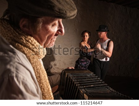 Two European tango dancers turning as squeezebox performer plays