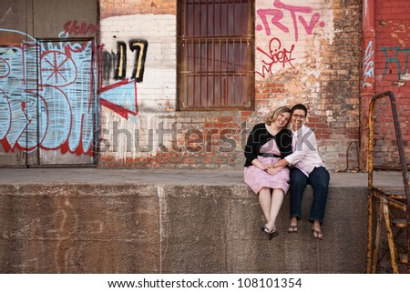 Two European women holding hands while sitting on a loading dock - stock photo