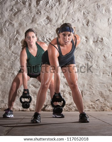 Two European women lifting heavy weights and sweating - stock photo