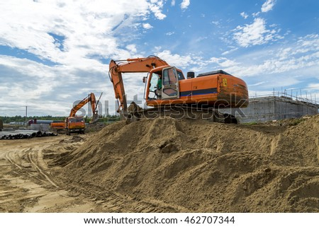 Two excavators digging in the sand against the sky