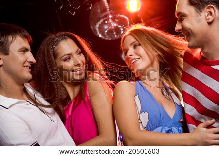 Two excited couples looking at each other with smiles during disco