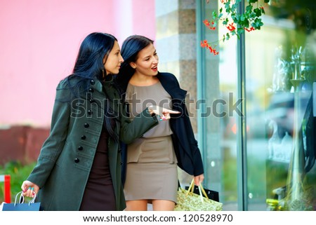 two excited elegant women looking in shop window - stock photo