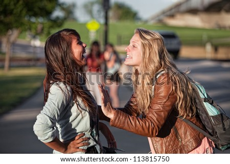 Two excited female teenage students talking outside - stock photo