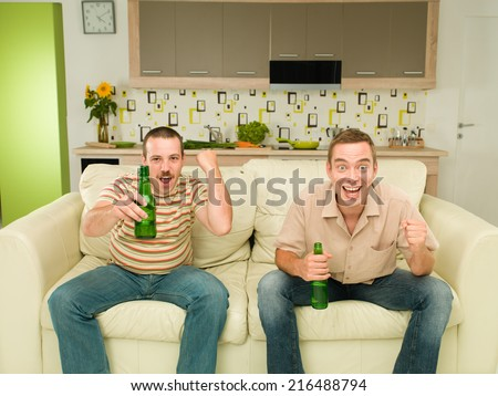 two excited men sitting on couch watching television, in kitchen, holding bears and screaming - stock photo