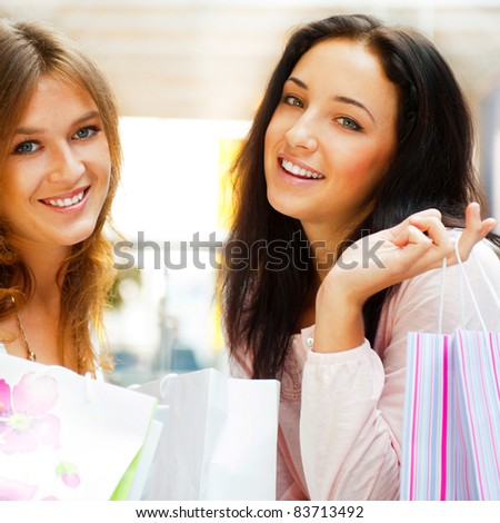 Two excited shopping woman together inside shopping mall. Horizontal Shot
