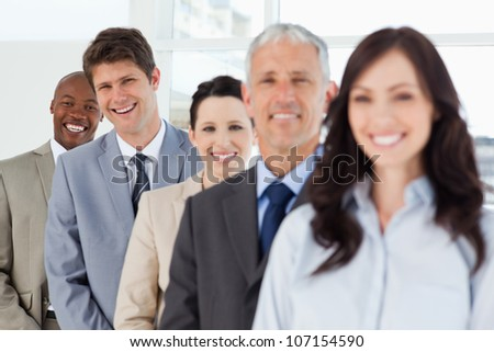 Two executives laughing in the background while following their full team - stock photo