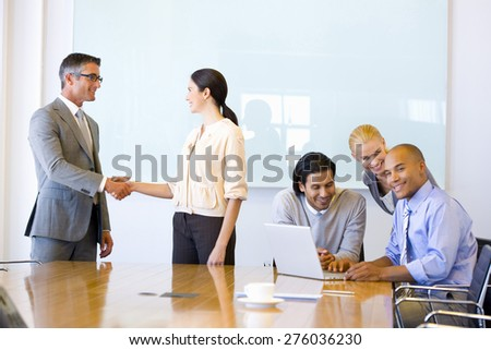 Two executives shaking hands in a meeting room with business team beside them. - stock photo