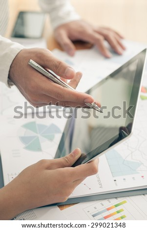 Two executives using digital tablet at the business meeting