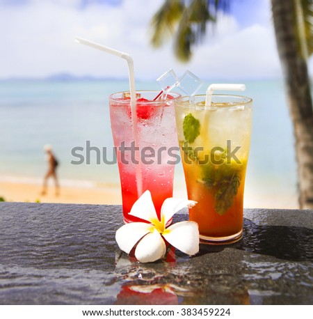 Two exotic cocktails in a tropical setting and the beach on the background - stock photo