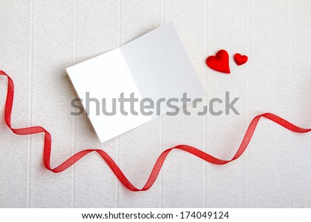 Two fabric hearts with an empty opened postcard and a red ribbon