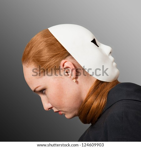 Two faces. Red head woman with white mask worn on the back of her head