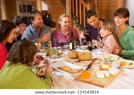 Two Familes Enjoying Meal In Alpine Chalet Together - stock photo