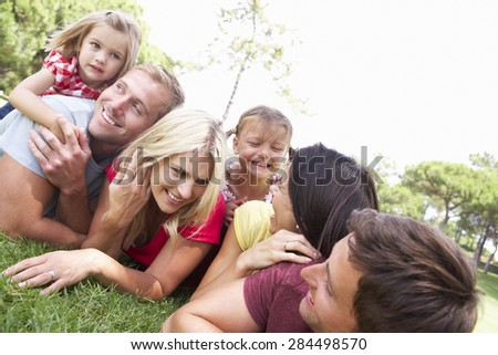 Two Families Playing In Park Together - stock photo