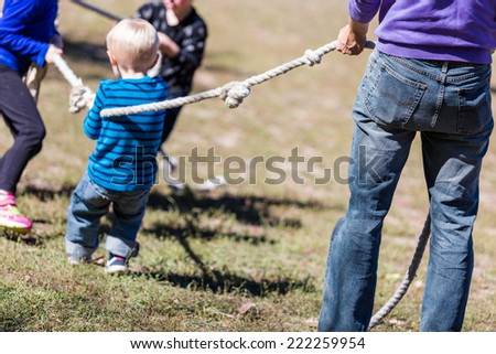 Two families playing vintage rope pulling game in the park.